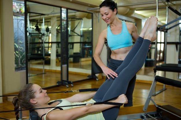 Kobieta trener pomagający kobiecie w ćwiczeniach rozciągających