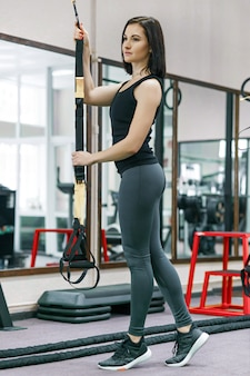 Kobieta treningu z systemem pętli fitness w siłowni