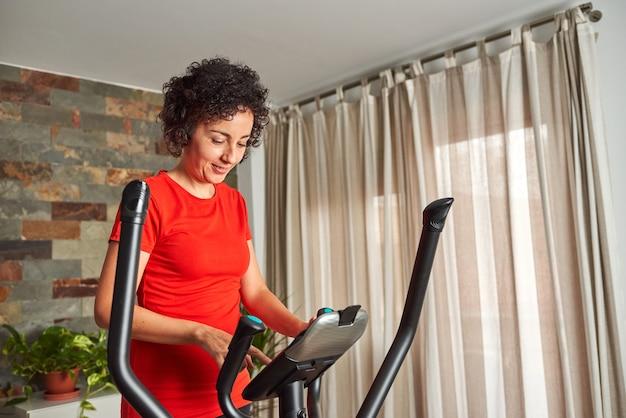 Kobieta trenująca w domu przy użyciu orbitreka