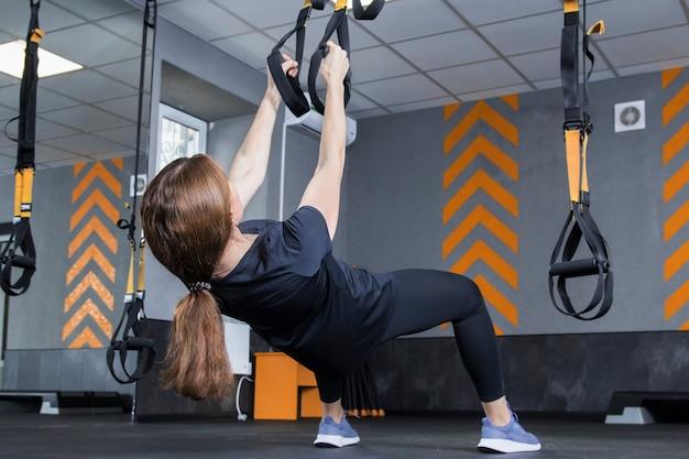 Kobieta trenująca z trx na siłowni, wykonująca trening fitness z pętlą na paskach.