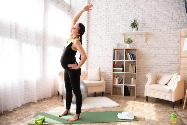 Kobieta trenuje brzuch w ciąży w domu.