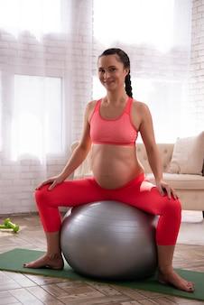 Kobieta trenuje ciężarnego brzucha na dużej piłce.