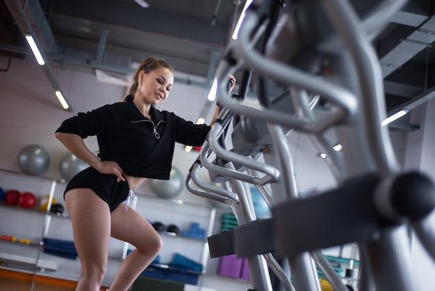 Kobieta trenuje na bieżni na siłowni.