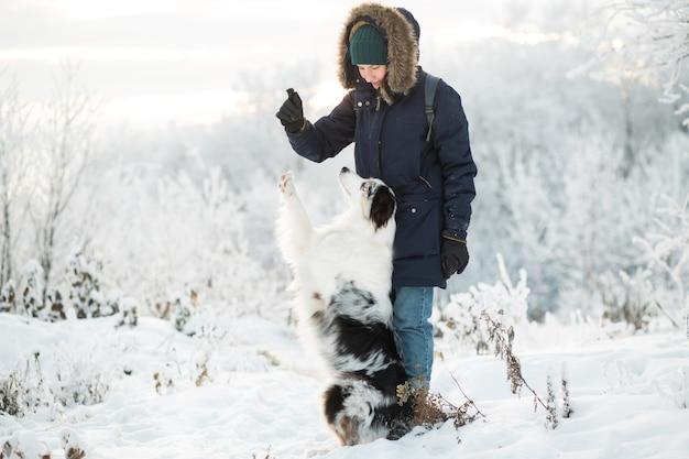 Kobieta trenuje owczarka australijskiego w zimowym lesie.