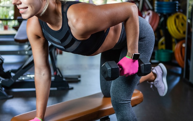 Kobieta trenuje plecy opierając się na ławce z hantlami w jednej ręce na siłowni. zdrowy tryb życia