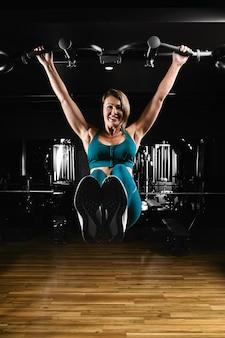 Kobieta trenuje prasy na poziomym pasku w siłowni