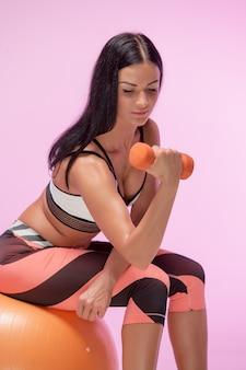 Kobieta trenuje przeciw różowemu studiu