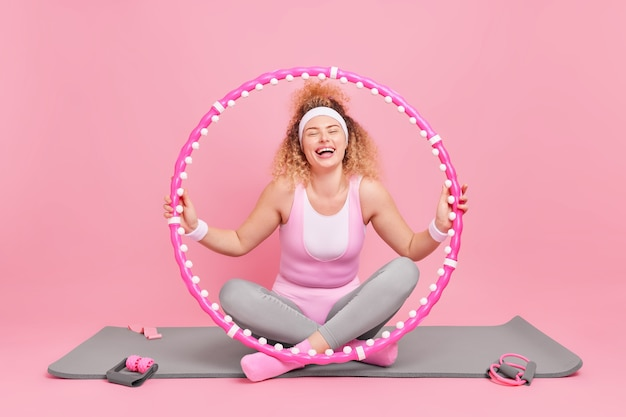 Kobieta trenuje z hula-hoopem ma dobry stan zdrowia piękny kształt ciała ma trening fitness na macie ćwiczenia regularnie prowadzi sportowy tryb życia