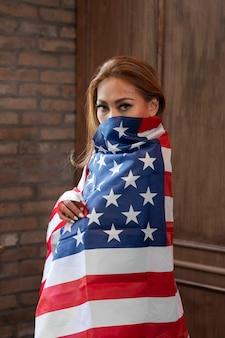 Kobieta trzyma amerykańską flagę średnio strzał