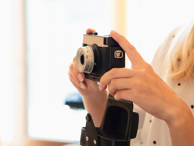 Kobieta trzyma aparat fotograficzny w stylu vintage
