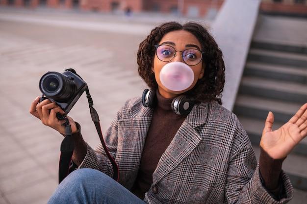 Kobieta trzyma aparat i dmuchanie baniek