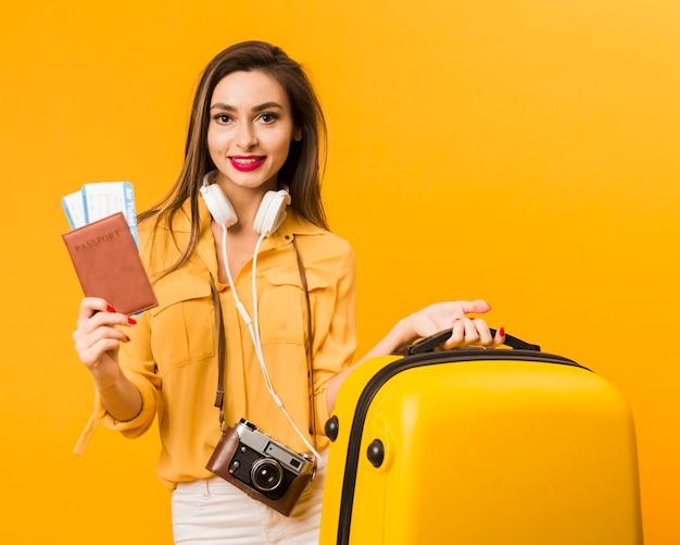 Kobieta trzyma bagaż i paszport z biletami lotniczymi