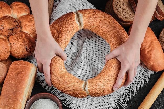 Kobieta trzyma bajgla na ciemnym stole z różnymi chlebami.