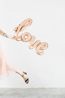 Kobieta trzyma balon foliowy miłości i odchodzi