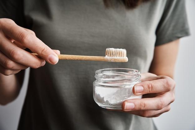 Kobieta trzyma bambusową szczoteczkę do zębów i proszek do zębów