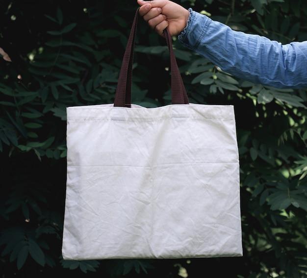 Kobieta trzyma bawełnianą ciężarową torbę na zielonym liścia tle ręka. koncepcja eco i recykling