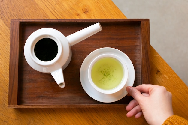 Kobieta trzyma białą filiżankę z japońską zieloną herbatą i teapot na ciemnej drewnianej porci tacy na stole, above. kawiarnia, styl życia