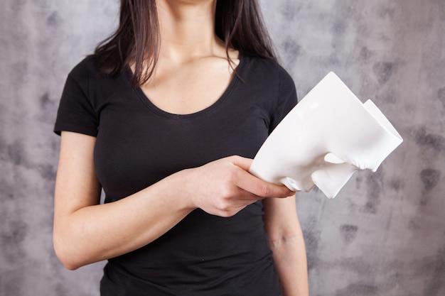 Kobieta trzyma białą plastikową maskę na szaro