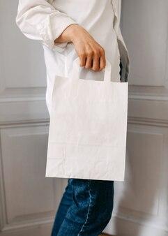 Kobieta trzyma białą pustą papierową torbę