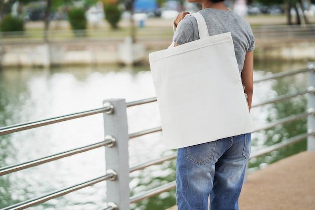 Kobieta trzyma białą pustą torbę