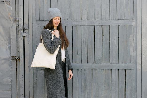 Kobieta trzyma białą tekstylną torbę ekologiczną w obszarze miejskim