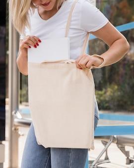 Kobieta trzyma białą torbę na zakupy i stojąc