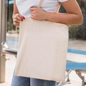 Kobieta trzyma białą torbę na zakupy w parku