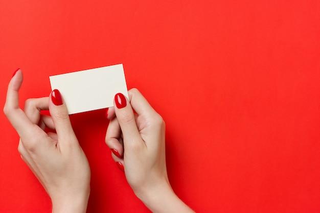 Kobieta trzyma białą wizytówkę makieta