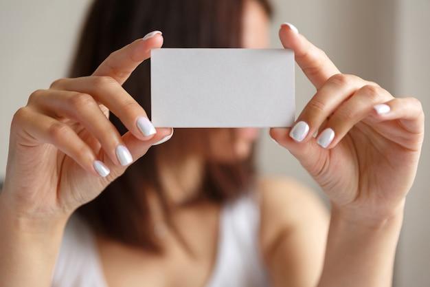 Kobieta trzyma białą wizytówkę w ręku, z bliska