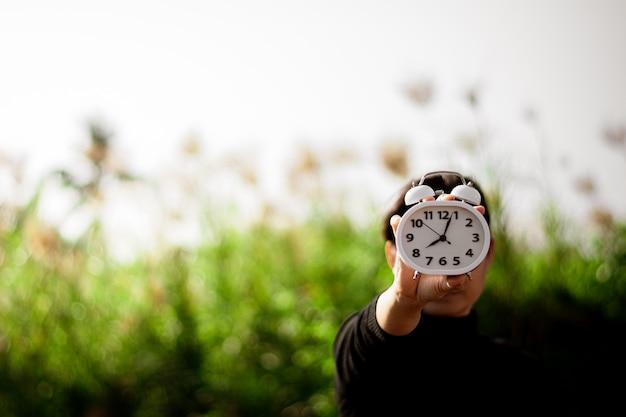 Kobieta trzyma białego budzika w ręce. myślenie i kontrola pomysłów na czas.