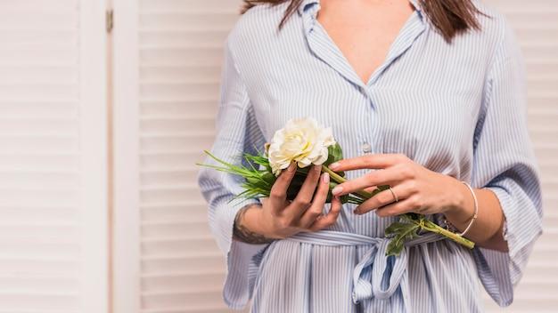 Kobieta trzyma białego kwiatu w błękit sukni