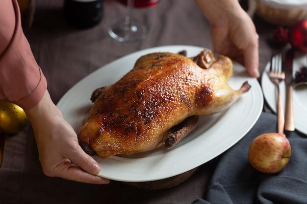 Kobieta trzyma biały talerz z crispy pieczoną kaczką, gotowe do podania