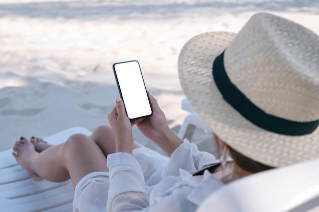 Kobieta trzyma biały telefon komórkowy z pustym ekranem, kładąc się na leżaku na plaży