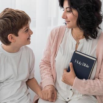 Kobieta trzyma biblię z dzieckiem