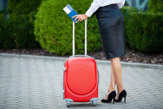 Kobieta trzyma bilety lotnicze w pobliżu lotniska w paszporcie.