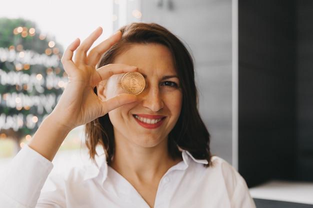 Kobieta trzyma bitcoina przed jej okiem. piękna kobieta głowa z bitcoin pieniądze w jej oku. kryptowaluta bitcoin.