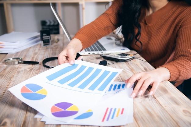 Kobieta trzyma biznesowy wykres z laptopem na stole roboczym