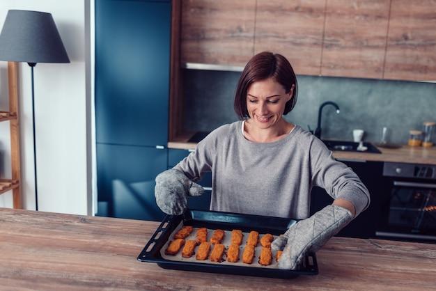 Kobieta trzyma blachę do pieczenia z podpartymi samorodkami kurczaka