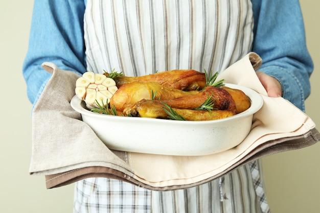 Kobieta trzyma blachę do pieczenia z podudziami pieczonego kurczaka