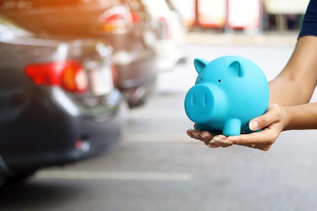 Kobieta trzyma błękitnego prosiątko banka