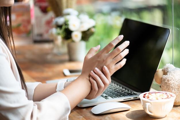 Kobieta trzyma ból nadgarstka z wykorzystaniem komputera. zespół biurowy