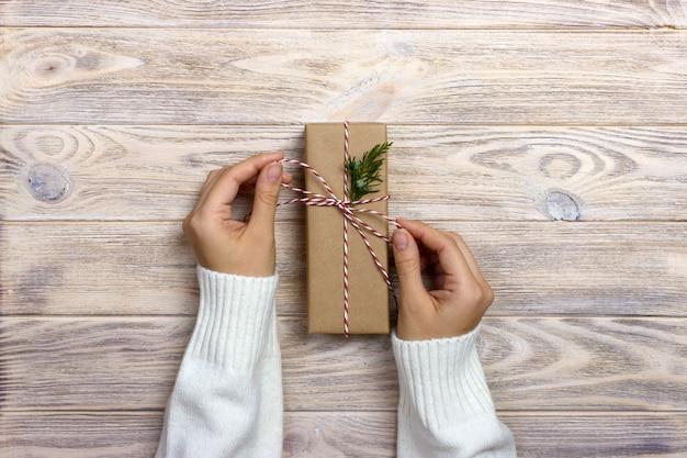 Kobieta trzyma boże narodzenie prezent w ręce na drewnianej powierzchni
