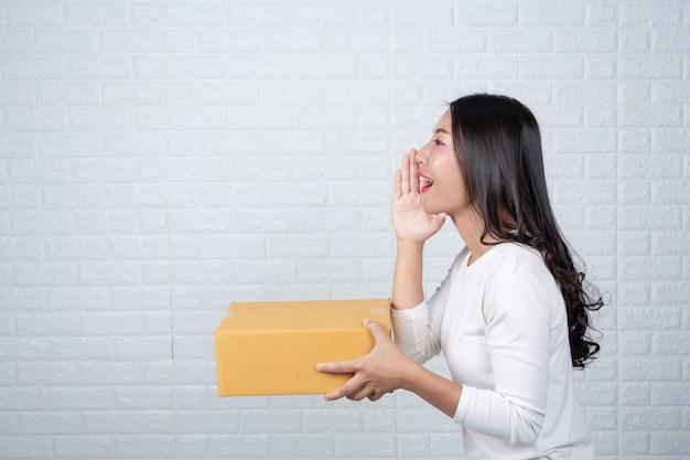 Kobieta trzyma brązową skrzynkę pocztową wykonał gesty z języka migowego.