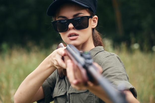 Kobieta trzyma broń w okularach przeciwsłonecznych