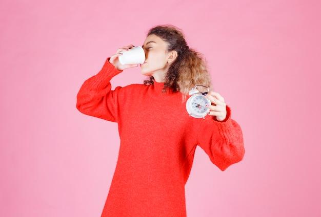 Kobieta trzyma budzik i picia kawy.