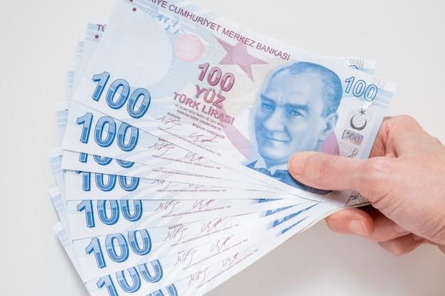 Kobieta trzyma bukiet 100 banknotów liry tureckiej