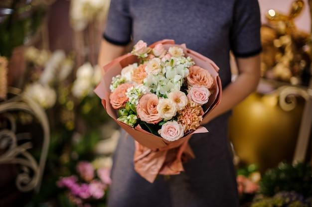 Kobieta trzyma bukiet beżowych róż i innych kwiatów