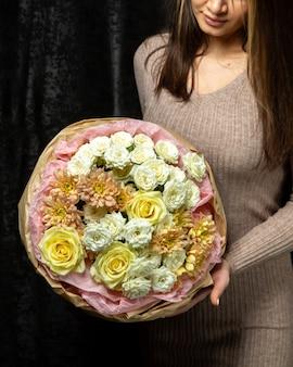 Kobieta trzyma bukiet białych i żółtych róż