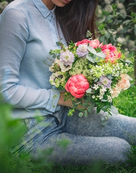 Kobieta trzyma bukiet kolorowych kwiatów letnich i siedzi na trawie.