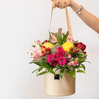 Kobieta trzyma bukiet kolorowych kwiatów w pudełku